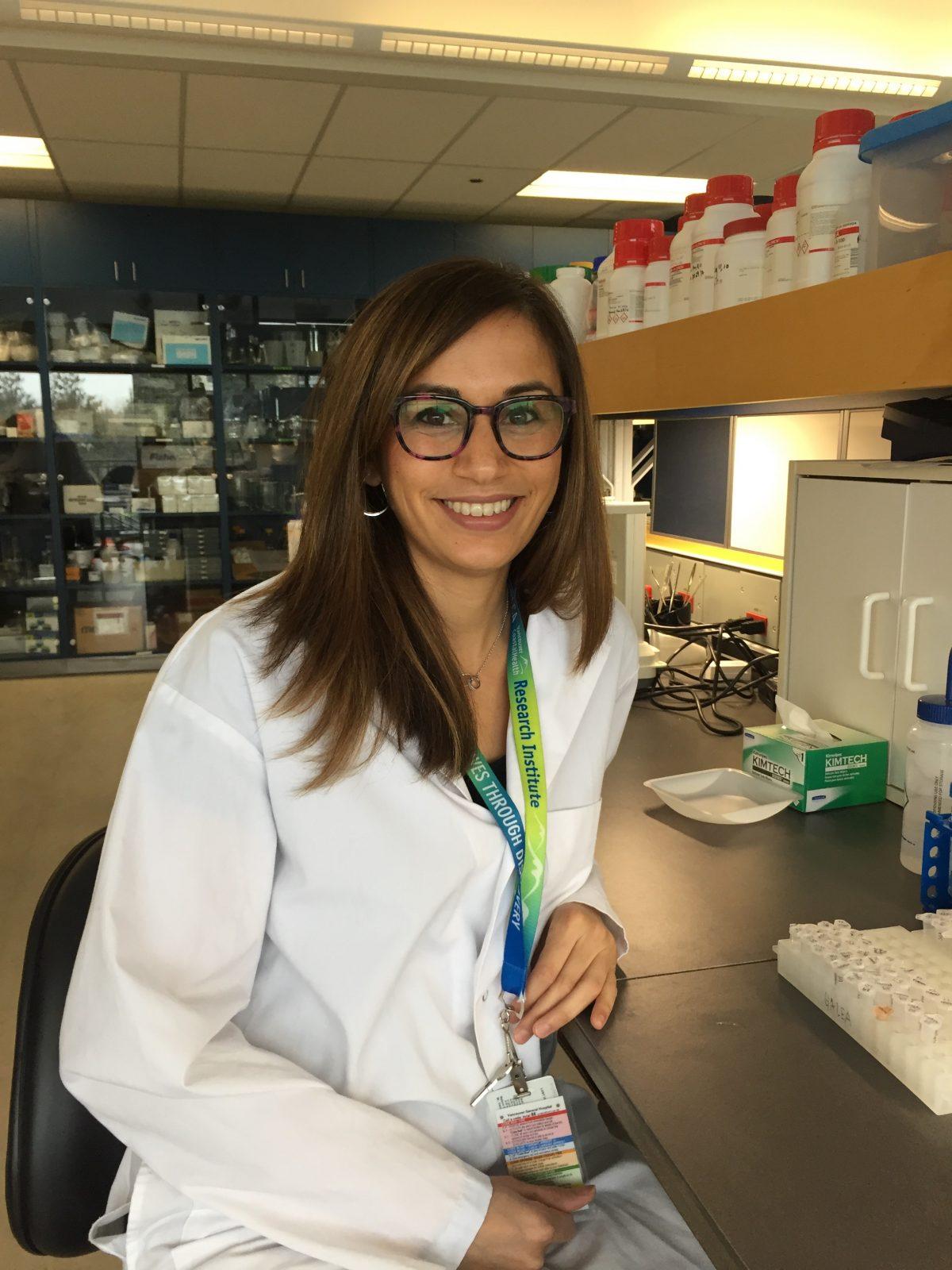 Dr. Cindy Barha sitting at desk wearing lab coat.